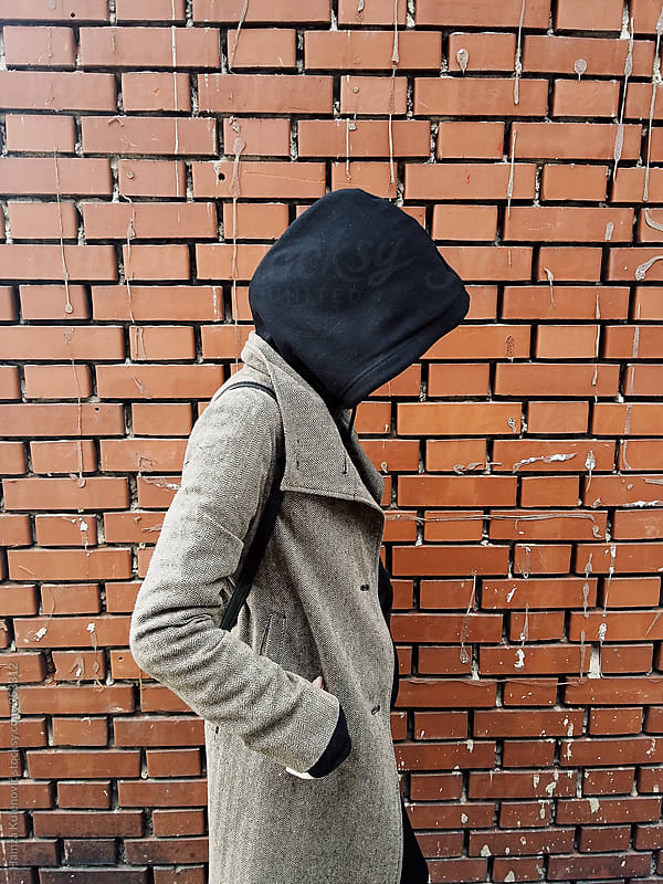 Young woman standing next to old brick wall by Hamza Kulenović for Stocksy United