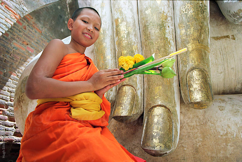 Close-up of Novice monk holding flowers at Hand of Buddha statue at Wat Si Chum. by Hugh Sitton for Stocksy United