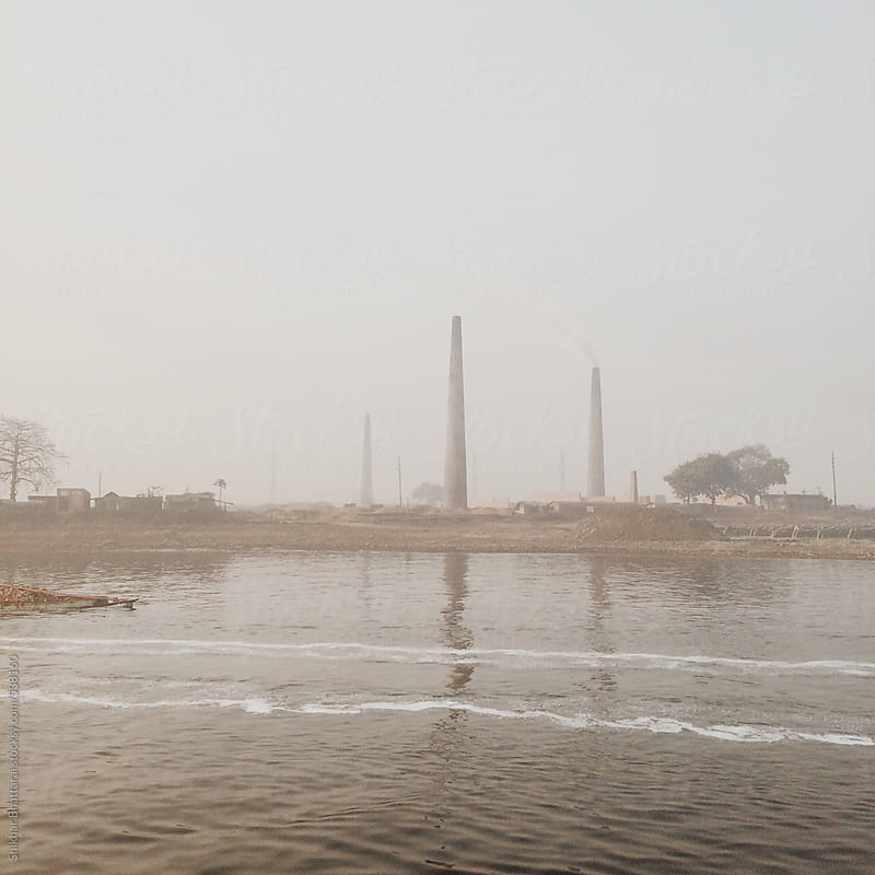 Polluted Buriganga river and brick factories on the riverbank in Dhaka, Bangladesh. by Shikhar Bhattarai for Stocksy United
