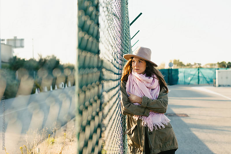 Portrait of a modern woman standing by a fence at sunrise. by BONNINSTUDIO for Stocksy United