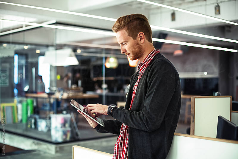 Young Businessman Using a Digital Tablet at Work by Lumina for Stocksy United