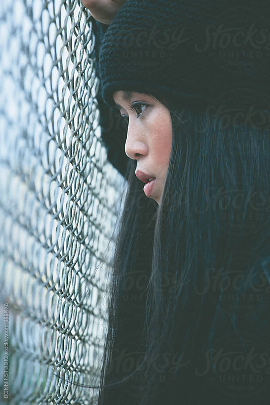 Chinese girl with wool cap near a metal fence. Winter scene on rooftop. by BONNINSTUDIO for Stocksy United