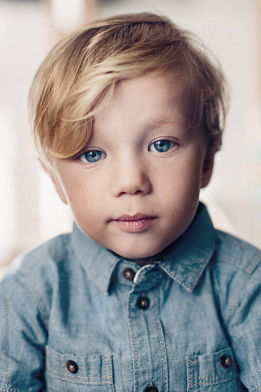 Portrait of a handsome serious little boy by Amir Kaljikovic for Stocksy United