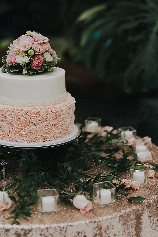 Detail of Blush Pink and White Wedding Cake on Candlelit Table by Alicia Magnuson Photography for Stocksy United