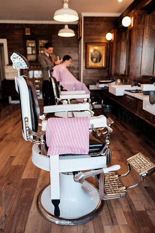 2 empty barber's chairs in foreground. Barber & client in background. by Riley Joseph for Stocksy United