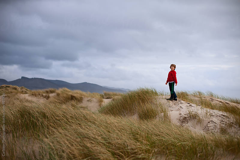 Boy stands atop a sand dune and looks back by Carleton Photography for Stocksy United