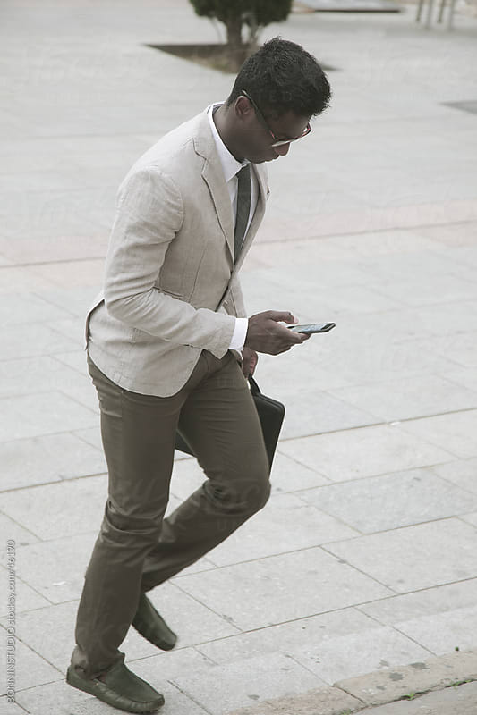 African young businessman up the stairs and sending a message on smartphone. by BONNINSTUDIO for Stocksy United
