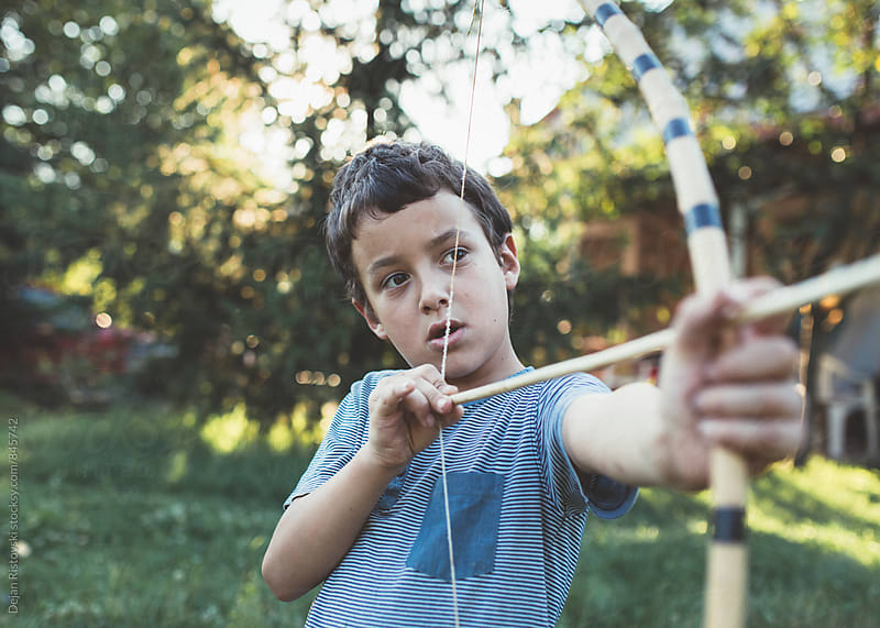 Boy playing with bow and arrow  by Dejan Ristovski for Stocksy United