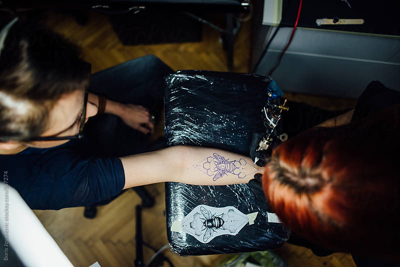 Above shot of female tattoo artist drawing a tattoo by Boris Jovanovic for Stocksy United