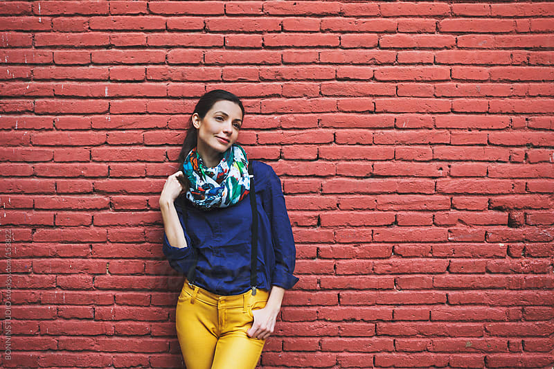 Beautiful woman standing in front red brick wall. by BONNINSTUDIO for Stocksy United