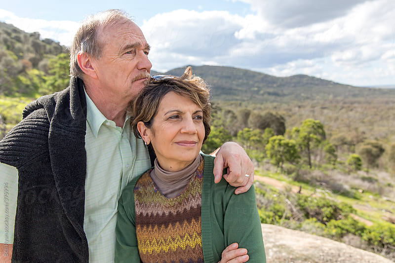 Grey nomad couple standing close on rocky outcrop with bushland backdrop by Ben Ryan for Stocksy United