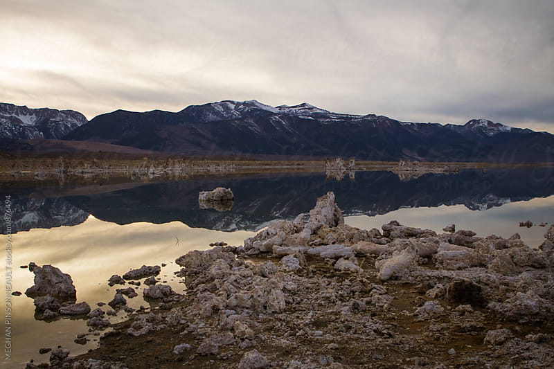 Snowy Mountains Reflecting on Winter Lake at Dusk by MEGHAN PINSONNEAULT for Stocksy United
