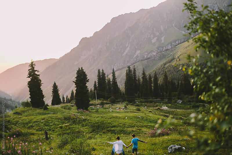 Young couple walking on the mountain top by Evgenij Yulkin for Stocksy United