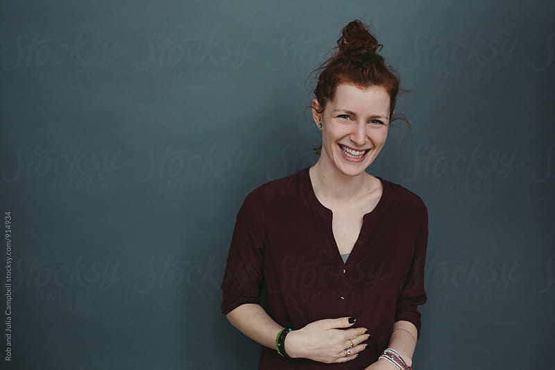 Happy candid portrait of young red head on solid grey blue background by Rob and Julia Campbell for Stocksy United