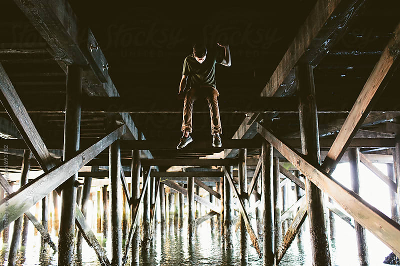 Young man sitting underneath bridge by Joe St.Pierre Photography for Stocksy United
