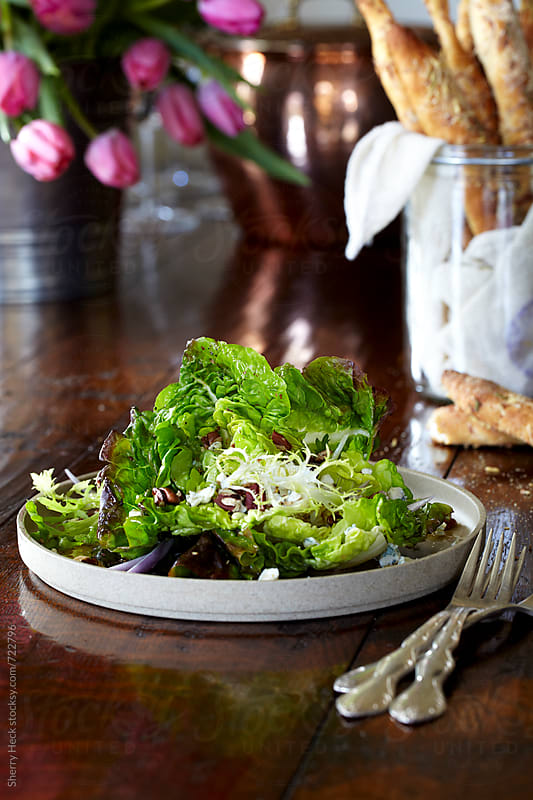 Plate of fresh bib lettuce salad on elegant wood table by Sherry Heck for Stocksy United