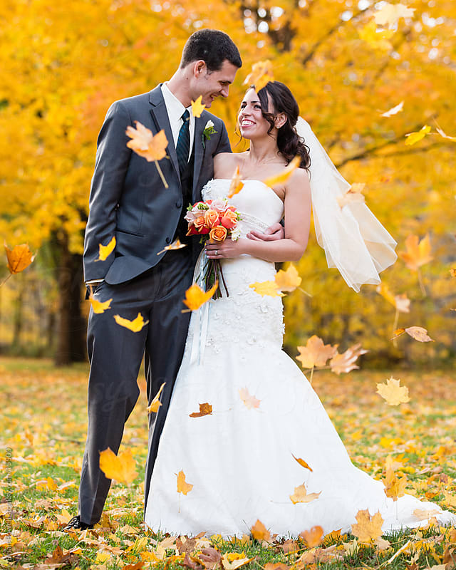 bride and groom in the fall by Brian Powell for Stocksy United