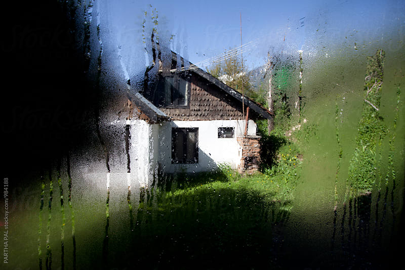 A house as seen from a window with water droplets on window glass by PARTHA PAL for Stocksy United
