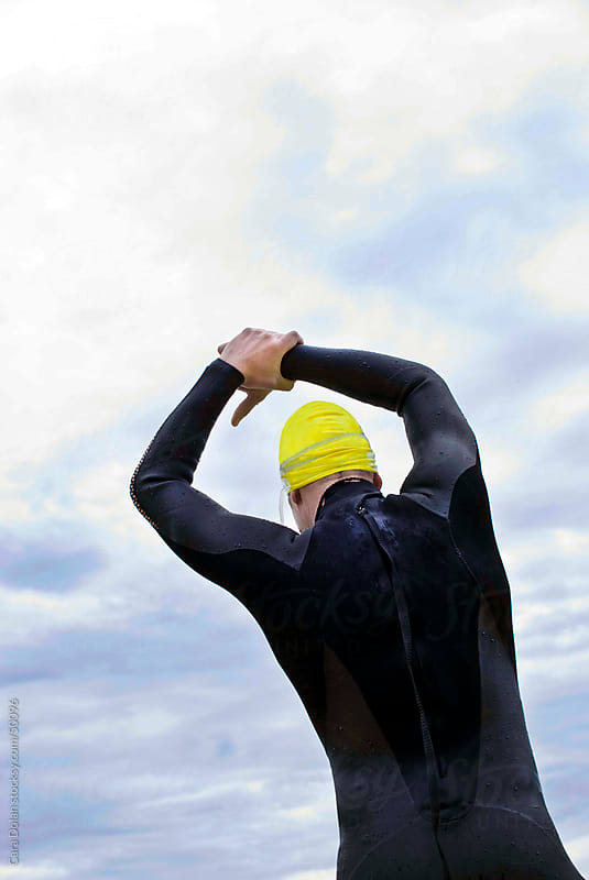 Swimmer in wet suit and swim cap stretches before the race by Cara Dolan for Stocksy United