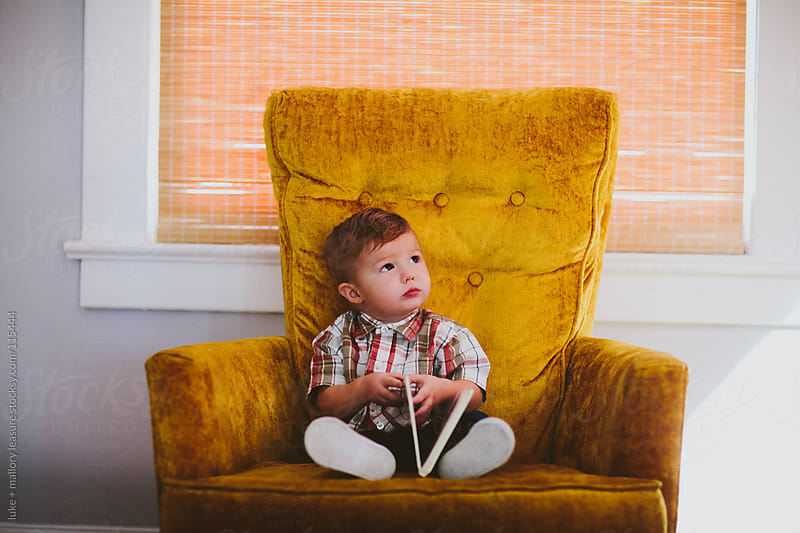 Toddler sitting on chair with book by luke + mallory leasure for Stocksy United