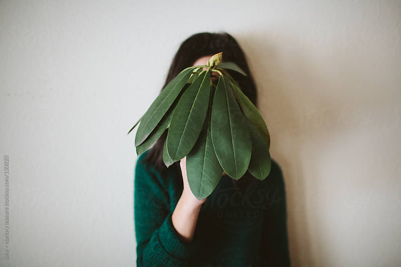 Girl holding plant in front of face by luke + mallory leasure for Stocksy United