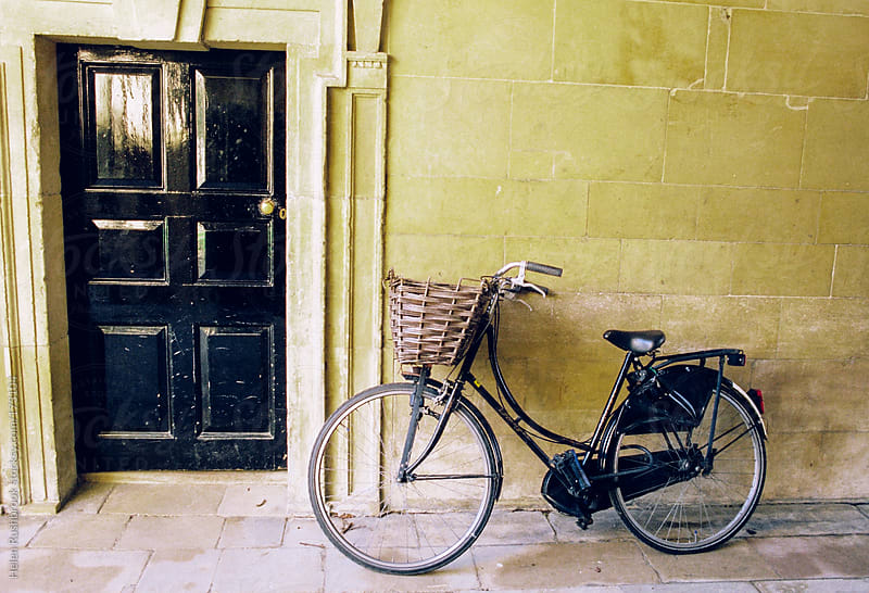 A bicycle leaning against a wall. by Helen Rushbrook for Stocksy United