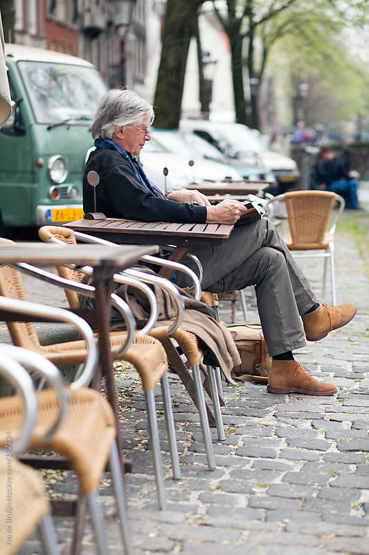 Pensioner relaxing and reading a book while sitting on a cobblestone road in Amsterdam by Ivo de Bruijn for Stocksy United