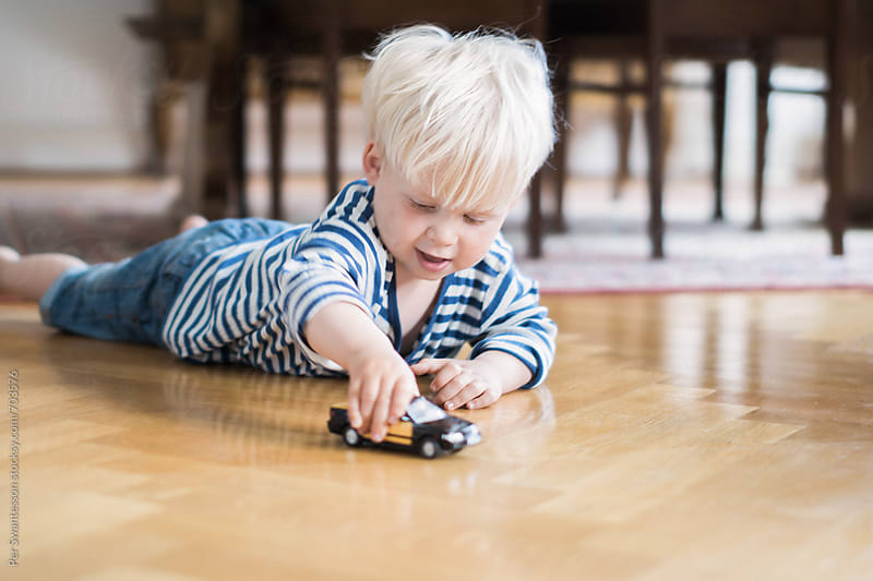 3 year old boy playing with toy car by Per Swantesson for Stocksy United
