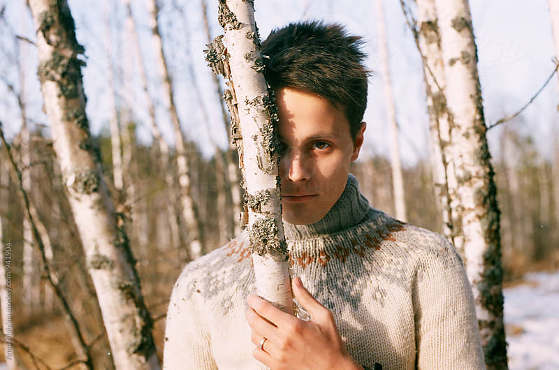 A film portrait of a young beautiful man hiding behind the tree by Anna Malgina for Stocksy United