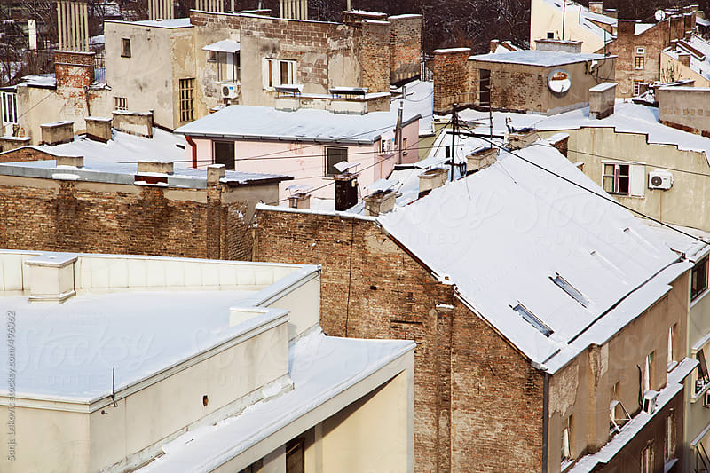buildings and rooftops covered with snow by Sonja Lekovic for Stocksy United