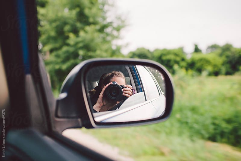 a woman taking a picture with a camera in a side car mirror by Sarah Lalone for Stocksy United