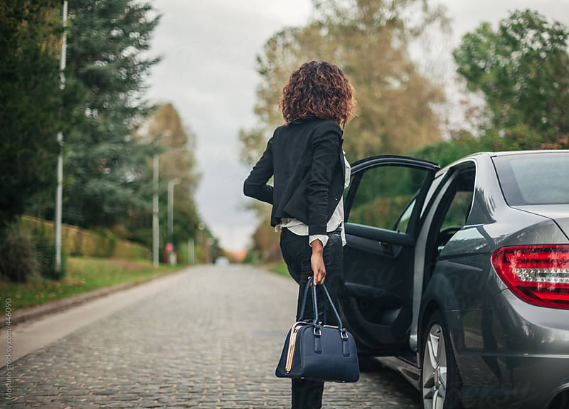 Woman Opening a Car Door  by Mosuno for Stocksy United