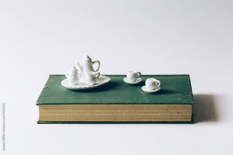 Tiny white tea set on vintage book by Jacqui Miller for Stocksy United
