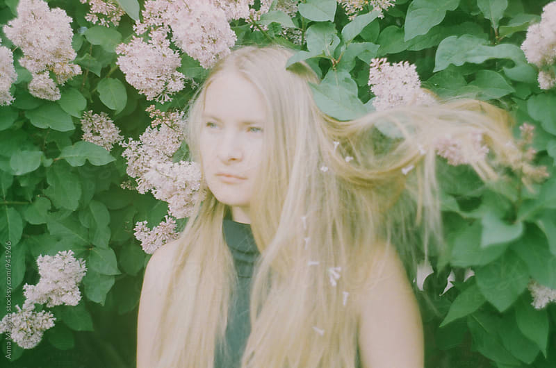 A film portrait of a young beautiful woman in the flowers by Anna Malgina for Stocksy United