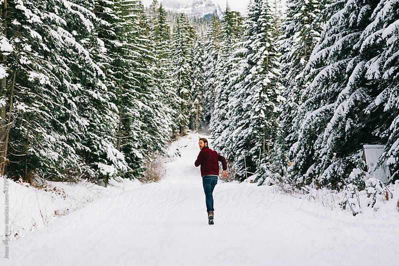 Young male runs down winter road by Jesse Morrow for Stocksy United