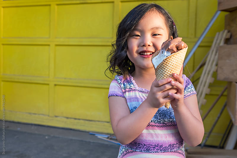 Happy Asian girl outdoor in the city holding ice cream by Suprijono Suharjoto for Stocksy United