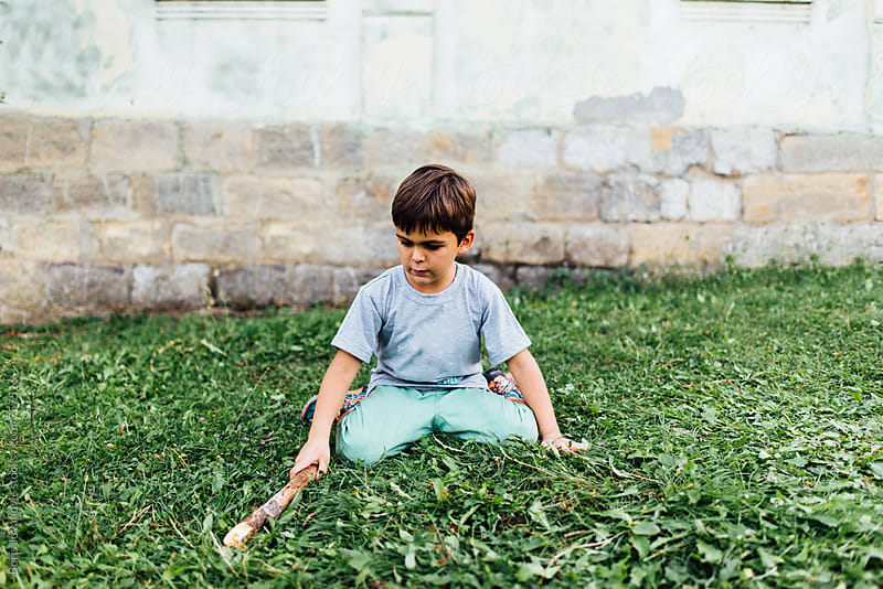 Young boy playing on the grass with a wooden stick by Boris Jovanovic for Stocksy United