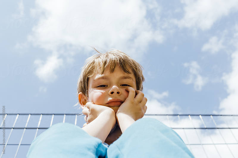 Preschooler boy portrait against cloudy sky by Mima Foto for Stocksy United