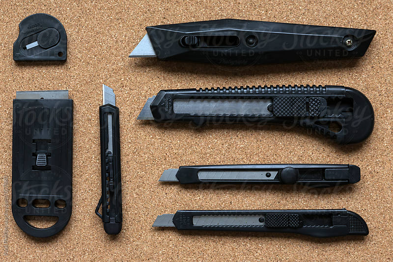 A selection of office knives on a cork background by Paul Phillips for Stocksy United