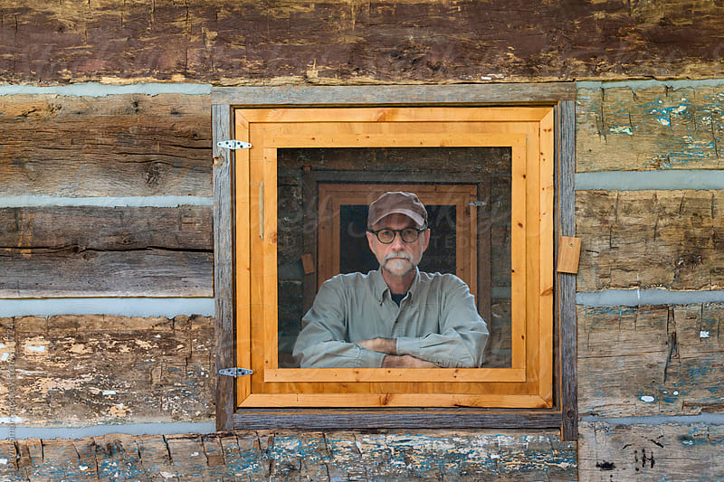 Older man looking at camera through an open window of a log cabin by David Smart for Stocksy United