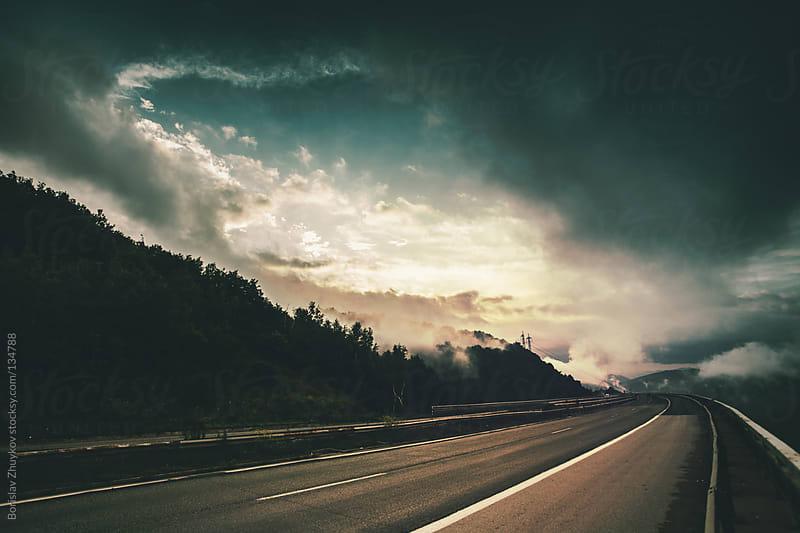 Empty highway road and stormy sky by Borislav Zhuykov for Stocksy United