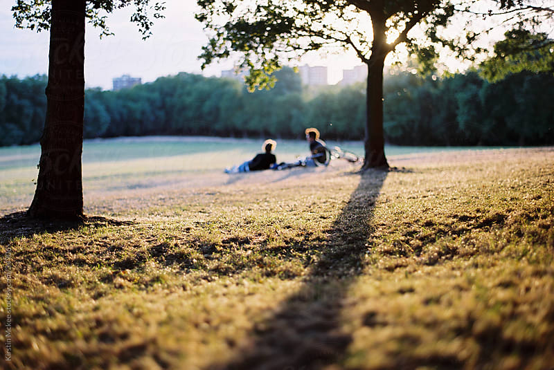 Friends relax on the grass in the park at sunset by Kirstin Mckee for Stocksy United