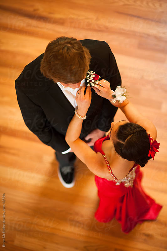 Prom: Young woman pins boutineer on her date by Brian McEntire for Stocksy United