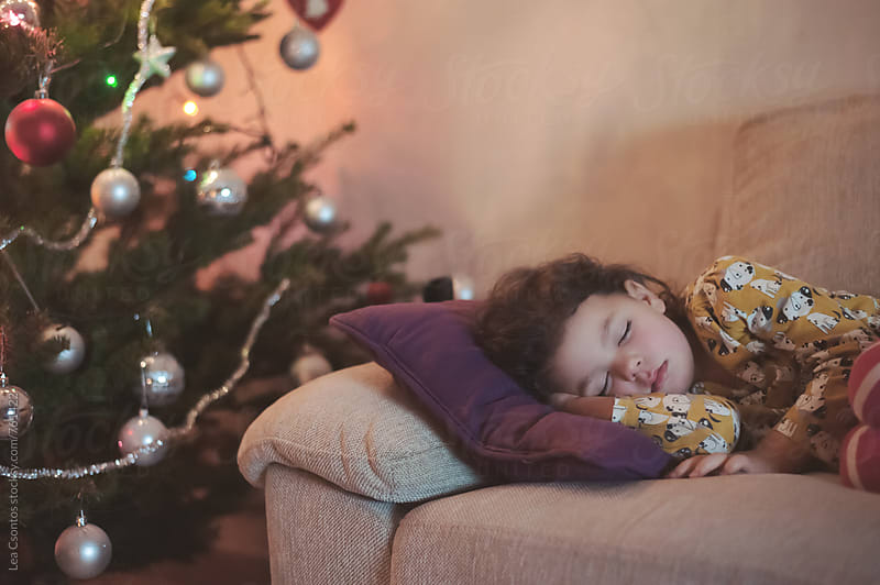 Little girl sleeping on a couch next to a christmas tree. by Lea Csontos for Stocksy United