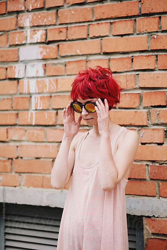 Young beautiful fashionable female in a pink dress puts on sunglasses  by Sergey Filimonov for Stocksy United