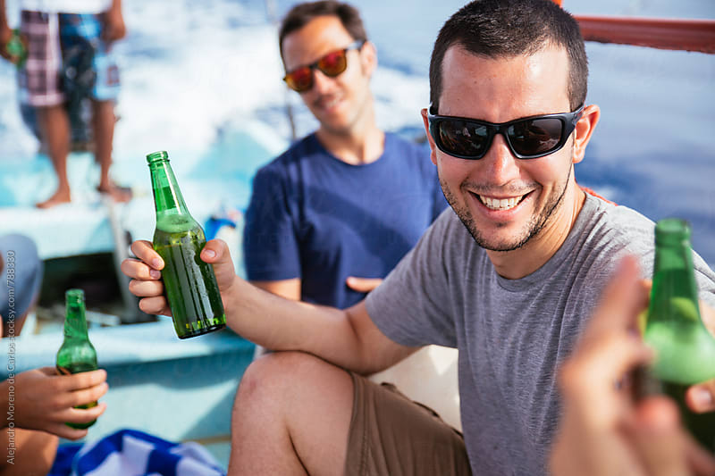 Young man smiling gathering with his friends and having some beers during a boat trip in the sea by Alejandro Moreno de Carlos for Stocksy United