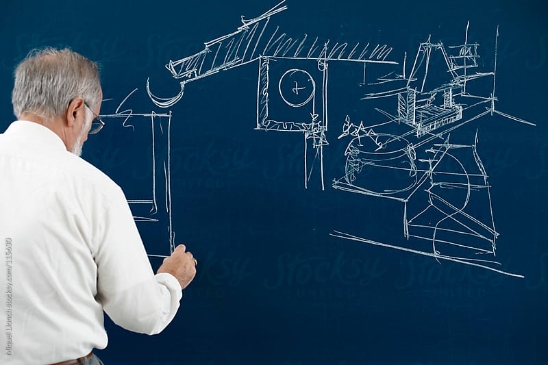 Mature professor drawing on the blackboard by Miquel Llonch for Stocksy United