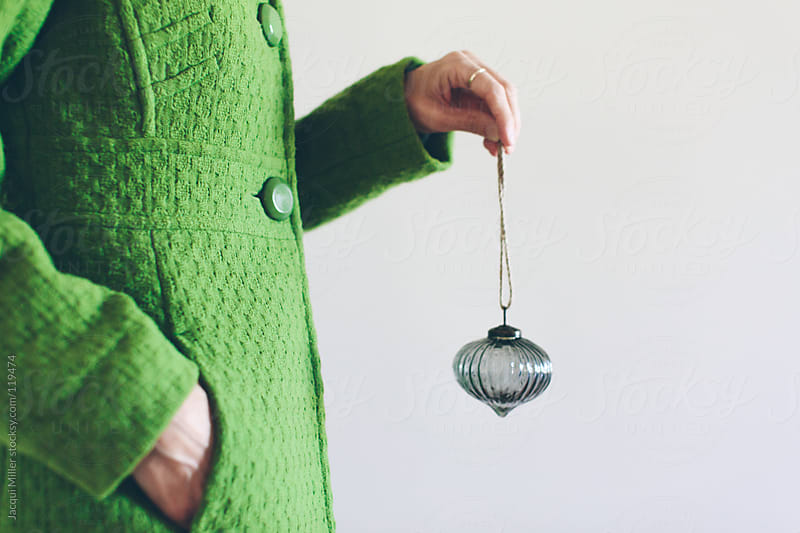 Woman wearing a bright green winter coat holds a glass Christmas ornament by Jacqui Miller for Stocksy United