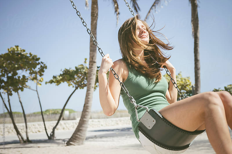 Young College Student Woman Having Fun on Swing during Spring Break in Miami by Joselito Briones for Stocksy United