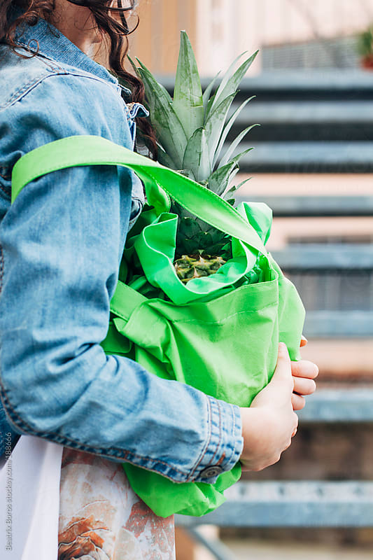 Girl with an ananas in her bag by Beatrix Boros for Stocksy United
